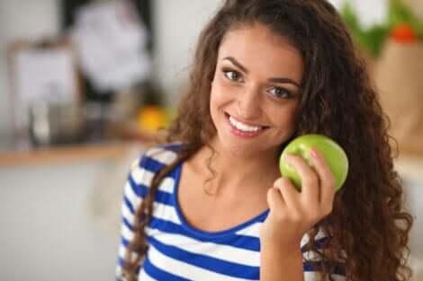 Donna che tiene in mano una mela.