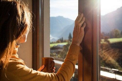 Donna guarda dalla finestra.
