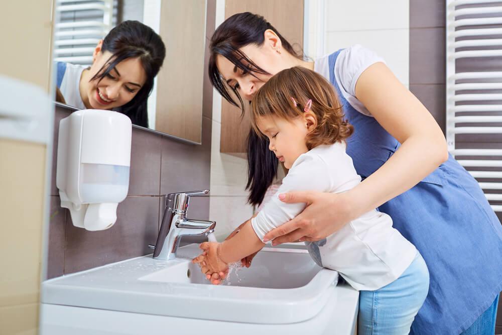 Mamma che fa lavare le mani alla figlia