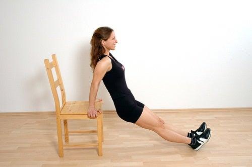 Donna che fa un esercizio con una sedia per tonificare le braccia