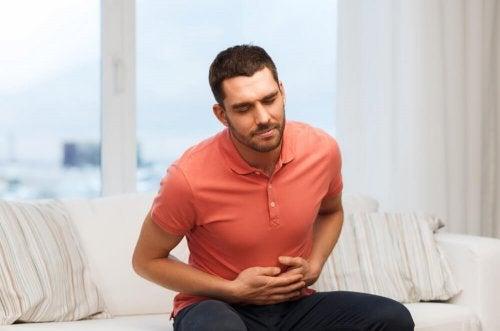 uomo seduto sul divano con mal di stomaco