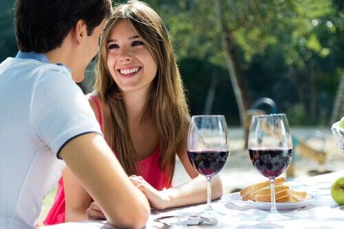 Coppia felice a tavola con calici di vino