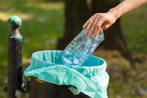 Donna che butta una bottiglia di plastica