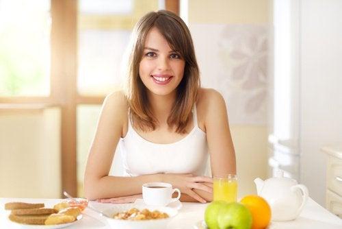 ragazza sorridente a tavola con alimenti per prima colazione