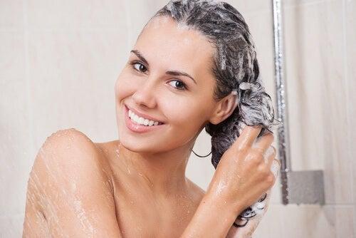 Donna con shampoo sotto la doccia