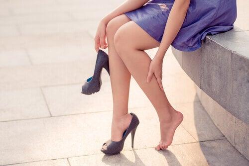 Donna con tacchi a spillo si massaggia le gambe