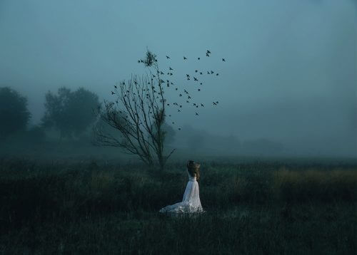 Donna davanti ad un albero spoglio con degli uccelli che volano