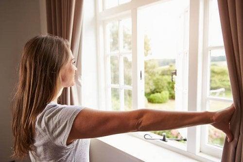 Donna davanti alla finestra di una stanza