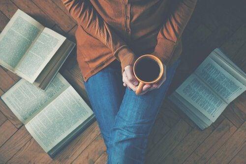 Donna seduta sul pavimento con un caffè e dei libri