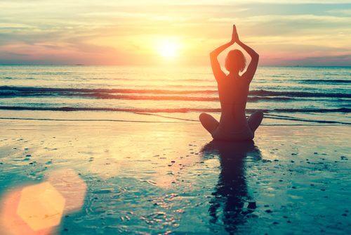 Donna che fa yoga in riva al mare
