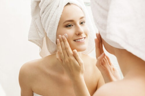 Donna che idrata la pelle del viso