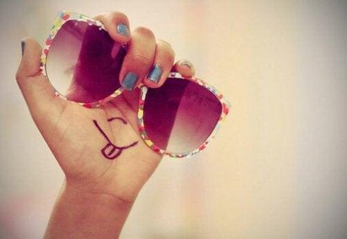 Mano con occhiali da sole e smile