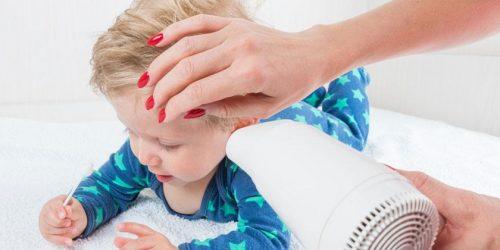 Donna asciuga con phon orecchie bambino