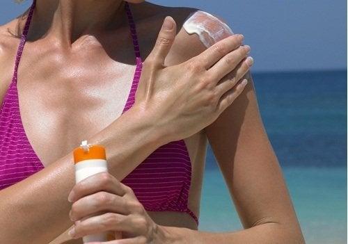 Donna che applica crema solare