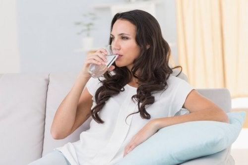 donna seduta sul divano beve acqua