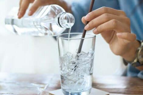 Donna che versa dell'acqua in un bicchiere.