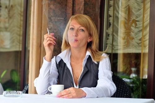 donna con una tazza di caffè fuma sigaretta