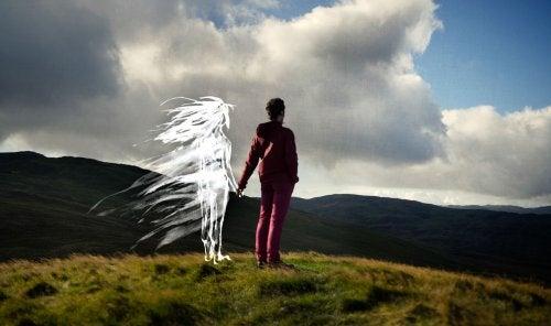 uomo in montagna dà la mano a donna invisibile