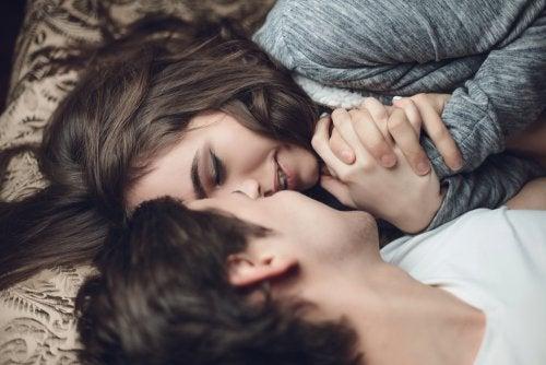 Coppia si bacia sul letto.