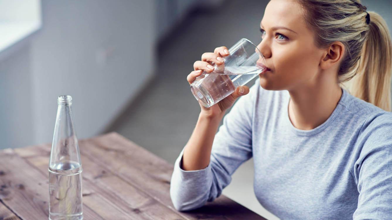 Donna beve un bicchiere d'acqua