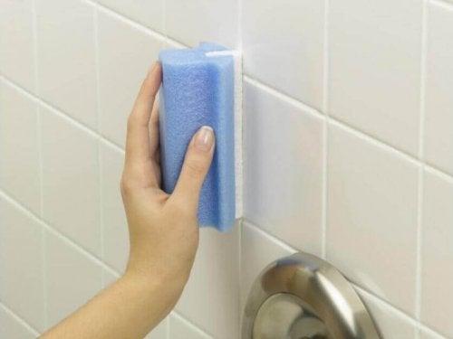 Donna che pulisce doccia e piastrelle