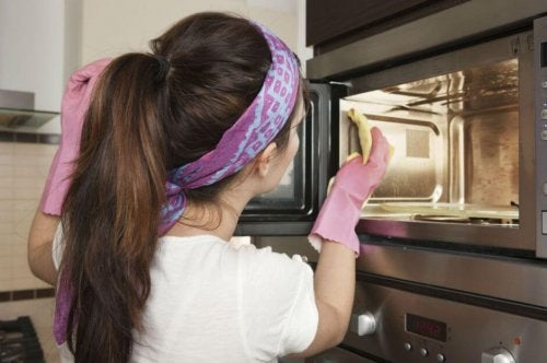 Donna che pulisce forno a microonde