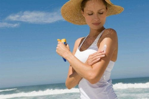 donna che si spalma protezione solare