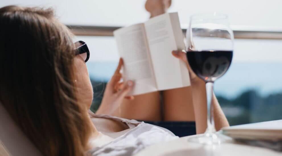 Donna con libro e calice di vino rosso