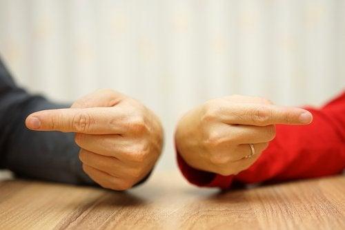 due persone con dita puntate verso se stesse