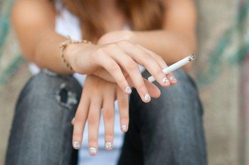 ragazza seduta con sigaretta in mano
