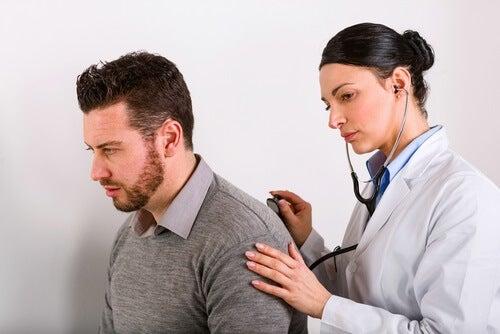 Medico ausculta i polmoni del paziente