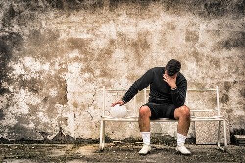 Uomo con pallone seduto su panchina smettere di sentirsi in colpa