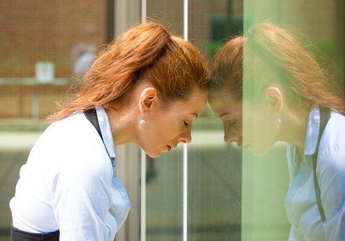 Donna con testa appoggiata su porta di vetro
