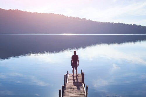 Uomo sul ponte di fronte all'acqua