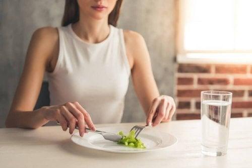 Ragazza a tavola con poca insalata nel piatto e bicchiere d'acqua