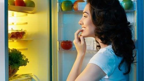 ragazza guarda dentro al frigorifero