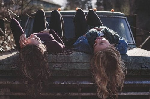 Amiche sdraiate sul cofano della macchina