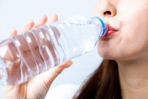ragazza beve acqua da bottiglia di plastica