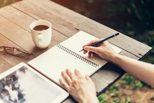 Donna che scrive con quaderno e tazza di caffè