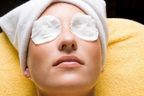 Donna con dischetti di cotone sugli occhi