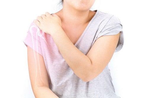 Donna con mal di spalla.