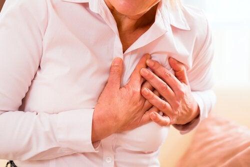 Donna con mano sul petto per infarto