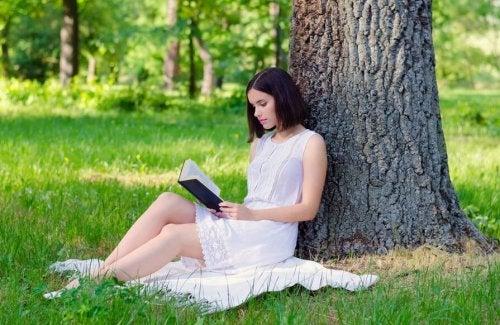 Donna che legge un libro sotto un albero