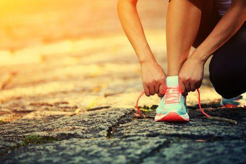 Donna sportiva mentre si lega la scarpa