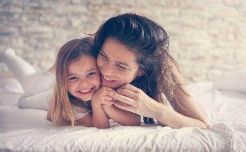 Madre e figlia abbracciate sul letto felici