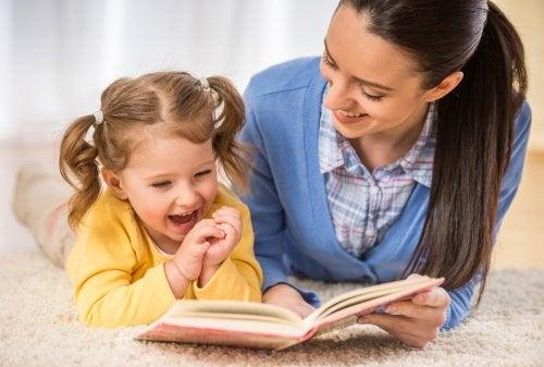 mamma e figlia leggono un libro sul tappeto