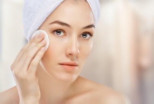 donna si pulisce il viso con un dischetto di cotone