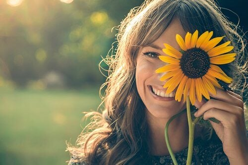 Ragazza che sorride con girasole in mano