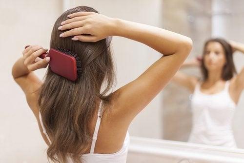 ragazza si spazzola i capelli mentre si guarda allo specchio