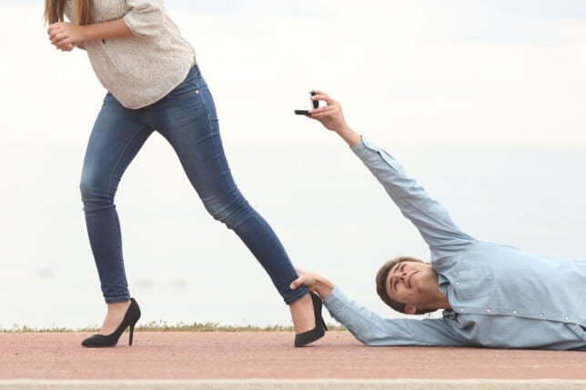 Uomo aggrappato alla caviglia della partner